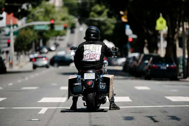 A motorcyclist advocating for rent strikes sits at a stoplight in San Francisco in May. With people leaving the Bay Area, some tenants are paying rent but negotiating for a lower amount.