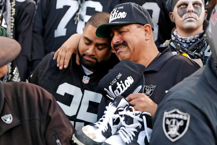 Oakland Raiders' fan Jesse Contrears cries as he hugs his son, Jesse, after Jacksonville Jaguars' 20-16 win during Raiders' final game at Oakland Coliseum in Oakland, Calif., on Sunday, December 15, 2019.