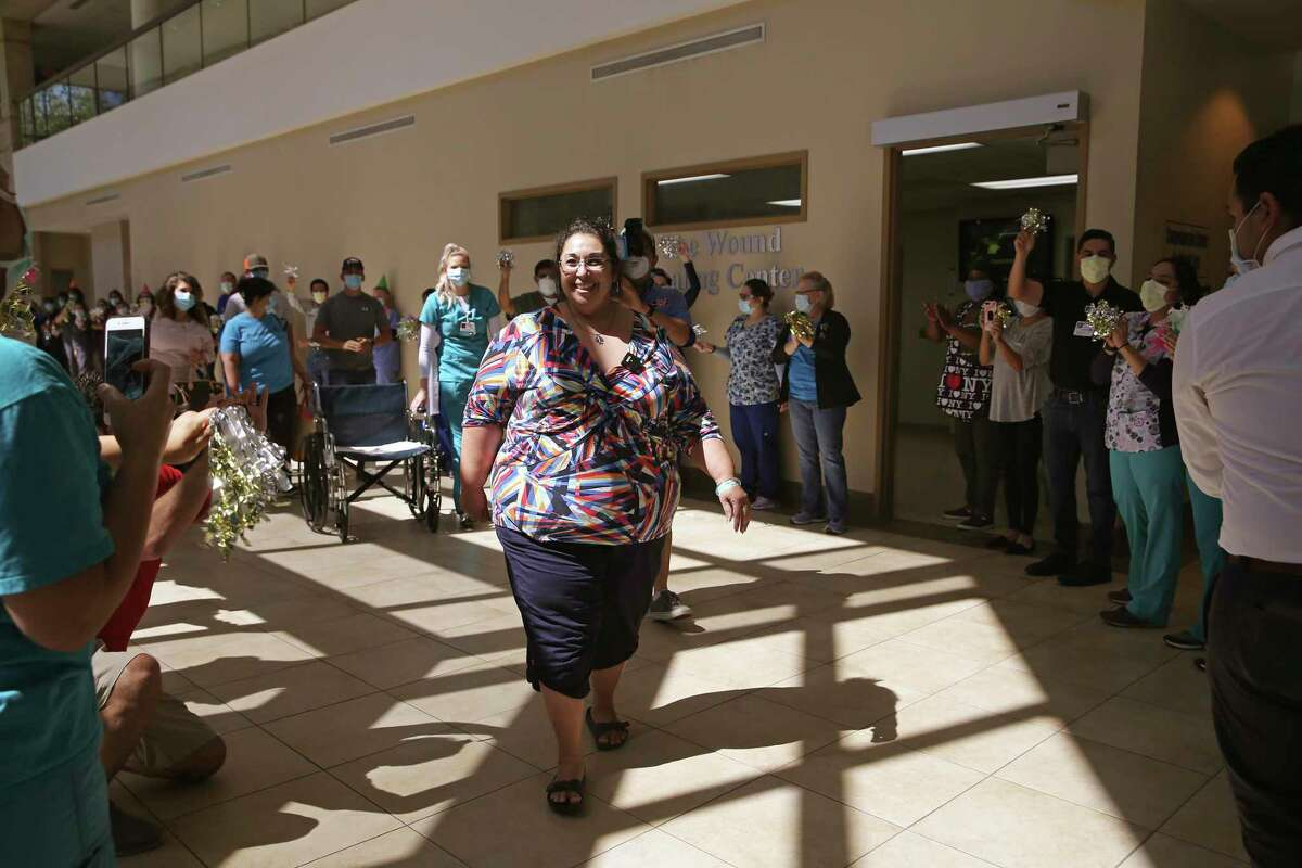 Northeast Baptist Hospital cheer Pamela Oakley as she walks out after surviving a near-fatal case of COVID-19. She spent three weeks on a ventilator and wasn't expected to survive.