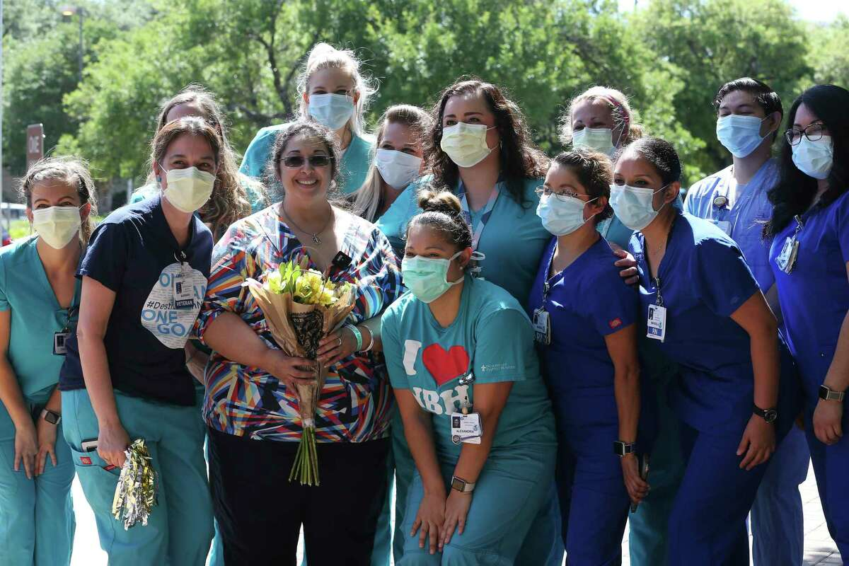 Pamela Oakley, 52, with flowers, poses with staff after her released from Northeast Baptist Hospital.