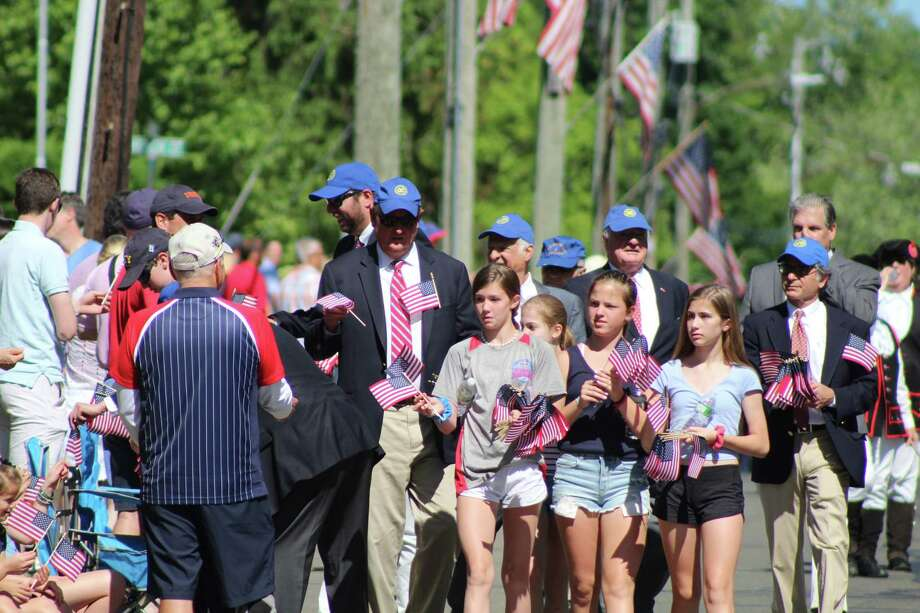 Exchange Club members (in the blue hats) Anthony Sillo, George Benington, Gayle Sanders, Marty McLaughlin, Tom McManus, Charlie Taben and Rich Carratu (without hat) were joined by family members and friends in handing out 5,000 flags to spectators along the Memorial Day Parade route in 2019. The 2020 parade was canceled Friday, May 1. Photo: John Kovach / Hearst Connecticut Media / Connecticut Post