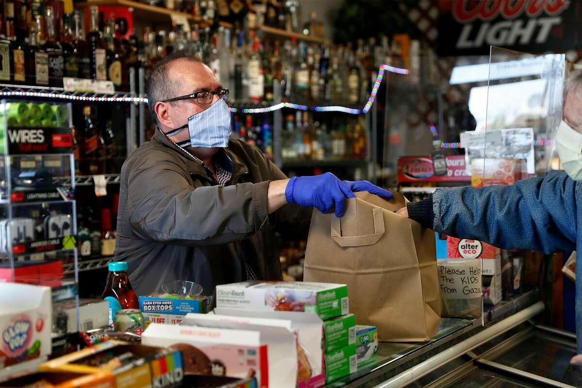 Duane Stephens packs a bag of groceries at Noe Hill Market in San Francisco, Calif., on Monday, April 13, 2020.