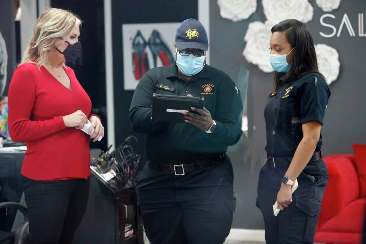 Amid concerns of the spread of COVID-19, City of Dallas officials finish up issuing a citation to salon owner Shelley Luther, left, for reopening her Salon A la Mode in Dallas, Friday, April 24, 2020. Hair salons have not been cleared for reopening in Texas. Luther was asked by the officials to close and was issued a citation when she refused. Luther said she will remain open for business. (AP Photo/LM Otero)
