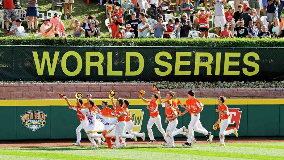 In this Sunday, Aug. 25, 2019, file photo, River Ridge, Louisiana, takes a victory lap around the field at Lamade Stadium after winning the Little League World Series Championship game against Curacao, 8-0, in South Williamsport, Pa. The 2020 Little League World Series and the championship tournaments in six other Little League divisions have been canceled because of the new coronavirus pandemic. (AP Photo/Gene J. Puskar, File) / Copyright 2019 The Associated Press. All rights reserved