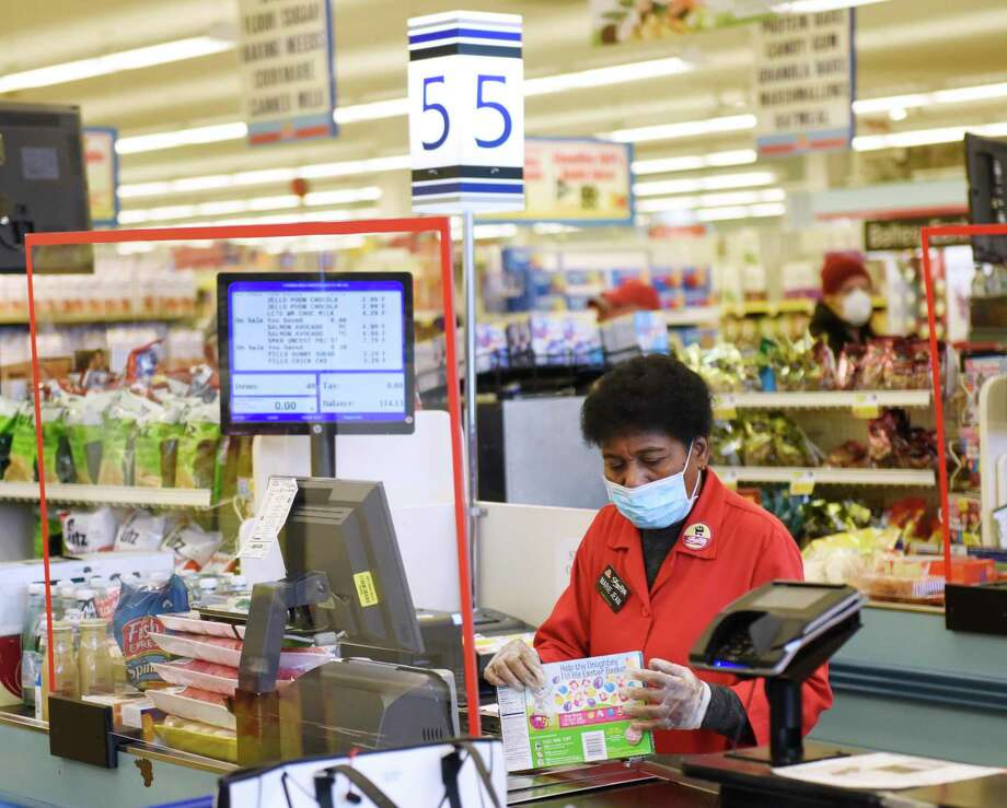 A sheet of plexiglass separates cashier Marie Jean from customers in line at ShopRite of Commerce St. in Stamford, Conn. Monday, March 30, 2020. Many grocery stores are taking precautions in preventing the spread of coronavirus including signs promoting social distancing and plexiglass between shoppers and cashiers. Photo: Tyler Sizemore / Hearst Connecticut Media / Greenwich Time