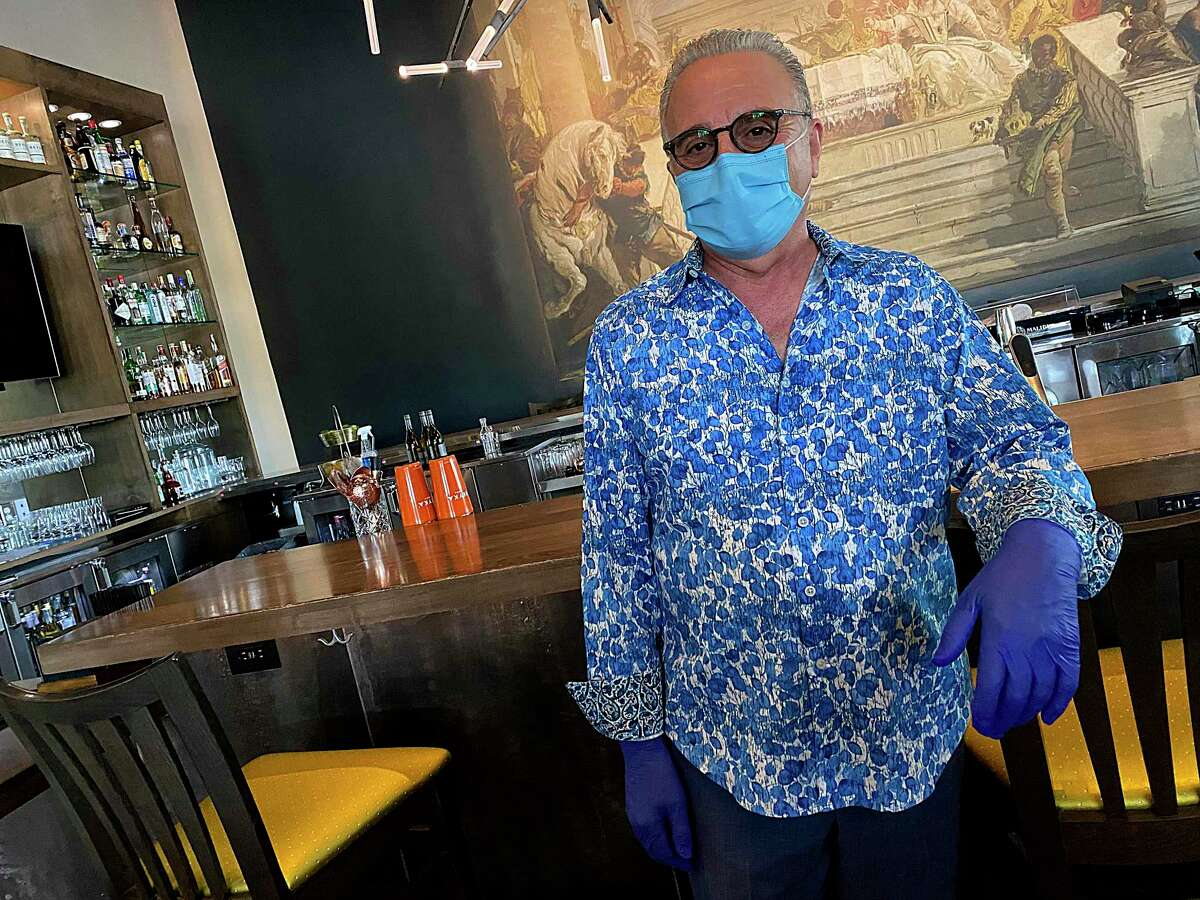Owner Aldo Ghaffari wore color-coordinated gloves and a protective mask as Aldo's Ristorante Italiano in the Dominion Ridge shopping center opened its dining room Friday for the first time since mid-March, operating under guidelines allowing no more than 25 percent occupancy as coronavirus crisis restrictions begin to lift in Texas.