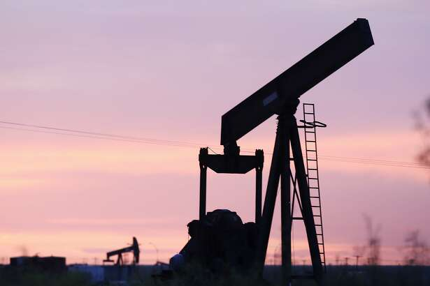 An oil pumpjack without its horesehead sits in a field as the sunsets in Penwell, Texas on Monday, April 27, 2020.