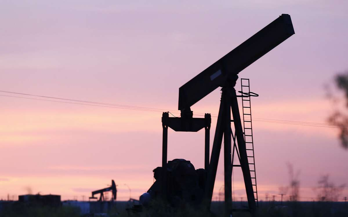 An oil pump jack without its horesehead sits in a field as the sunsets in Penwell, Texas, on Monday, April 27, 2020.