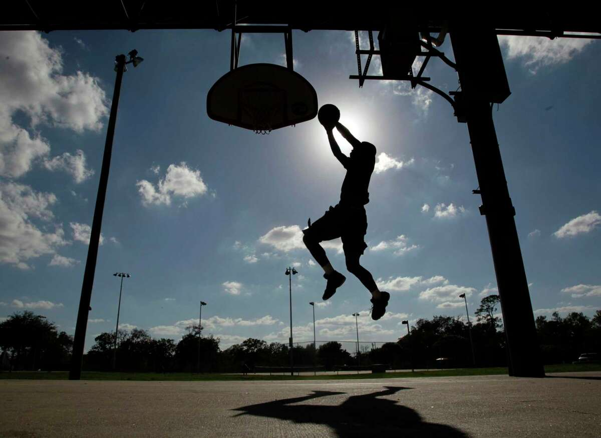 Dunta Jones, 19, puts up a shot while playing basketball at Moody Park Monday, Oct. 17, 2011, in Houston. Jones said he plays at the park every so often. Jones said he and two others were taking advantage of the cooler temperatures. ( Johnny Hanson / Houston Chronicle )