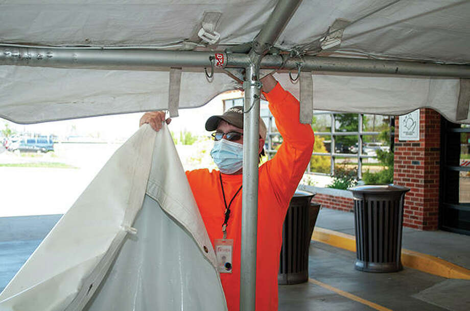 Roger Prior of O'Shea Builders works Friday to take down the triage tent outside Passavant Area Hospital's emergency room. The tent has been used for respiratory screening for the emergency department, but that screening now will move inside the west entrance. Photo: Darren Iozia | Journal-Courier