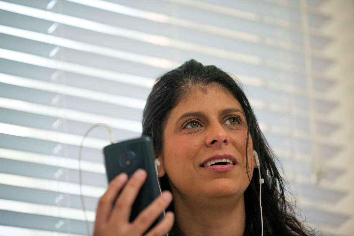 Trisha Behrens, 38, a former Bexar County detention deputy, video chats with her partner, John Garcia, who is currently incarcerated in the Bexar County jail after violating the terms of his parole. About 460 inmates are being held in the county jail on parole violations, according to county data.