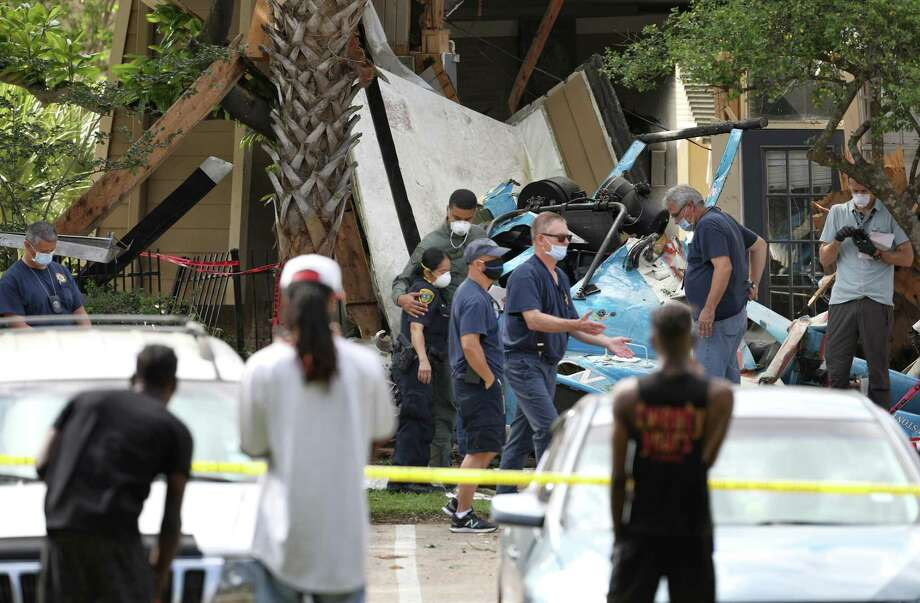 Two police officers hug as authorities investigate the scene where an HPD officer was killed and another was critically injured when a helicopter crashed into Greenspoint apartment complex Saturday, May 2, 2020, in Houston. Photo: Jon Shapley, Staff Photographer / Staff Photographer / © 2020 Houston Chronicle