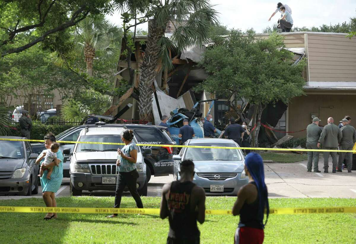 Authorities investigate the scene where an HPD officer was killed and another was critically injured when a helicopter crashed into Greenspoint apartment complex Saturday, May 2, 2020, in Houston.