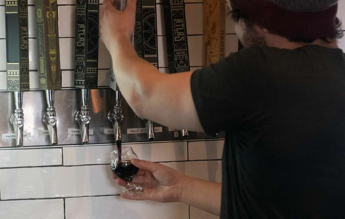 Head Brewer Daniel Vilarrubi pours a beer at Atlas Brew Works, a hand crafted artisanal beer brewery, in Washington, DC, December 20, 2019. - In bars across the United States, one product -- whether in bottles or on tap -- has become an absolute necessity for maintaining