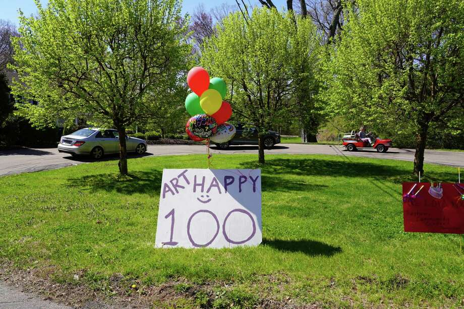 Art Bettauer was celebrated on his 100th Birthday with a surprise drive by his house in New Canaan on Saturday, May 2, 2020. His caregiver of five years, Jocelyne Gabriel, helped in the surprise. Photo: Grace Duffield / Hearst Connecticut Media
