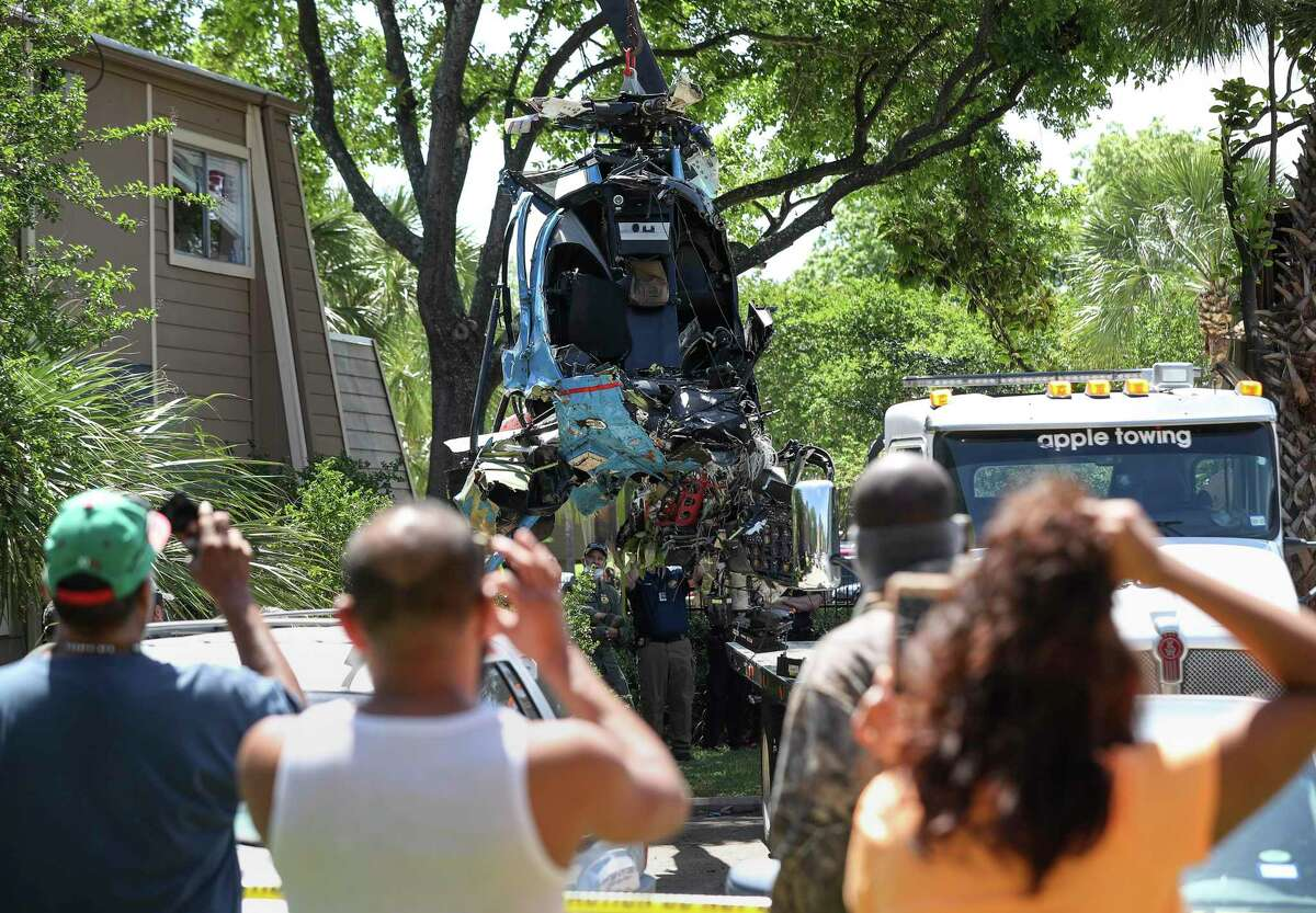 Authorities load an HPD helicopter onto a flatbed truck as they investigate the scene where an HPD officer was killed and another was critically injured when their helicopter crashed into a Greenspoint apartment complex Saturday, May 2, 2020, in Houston.