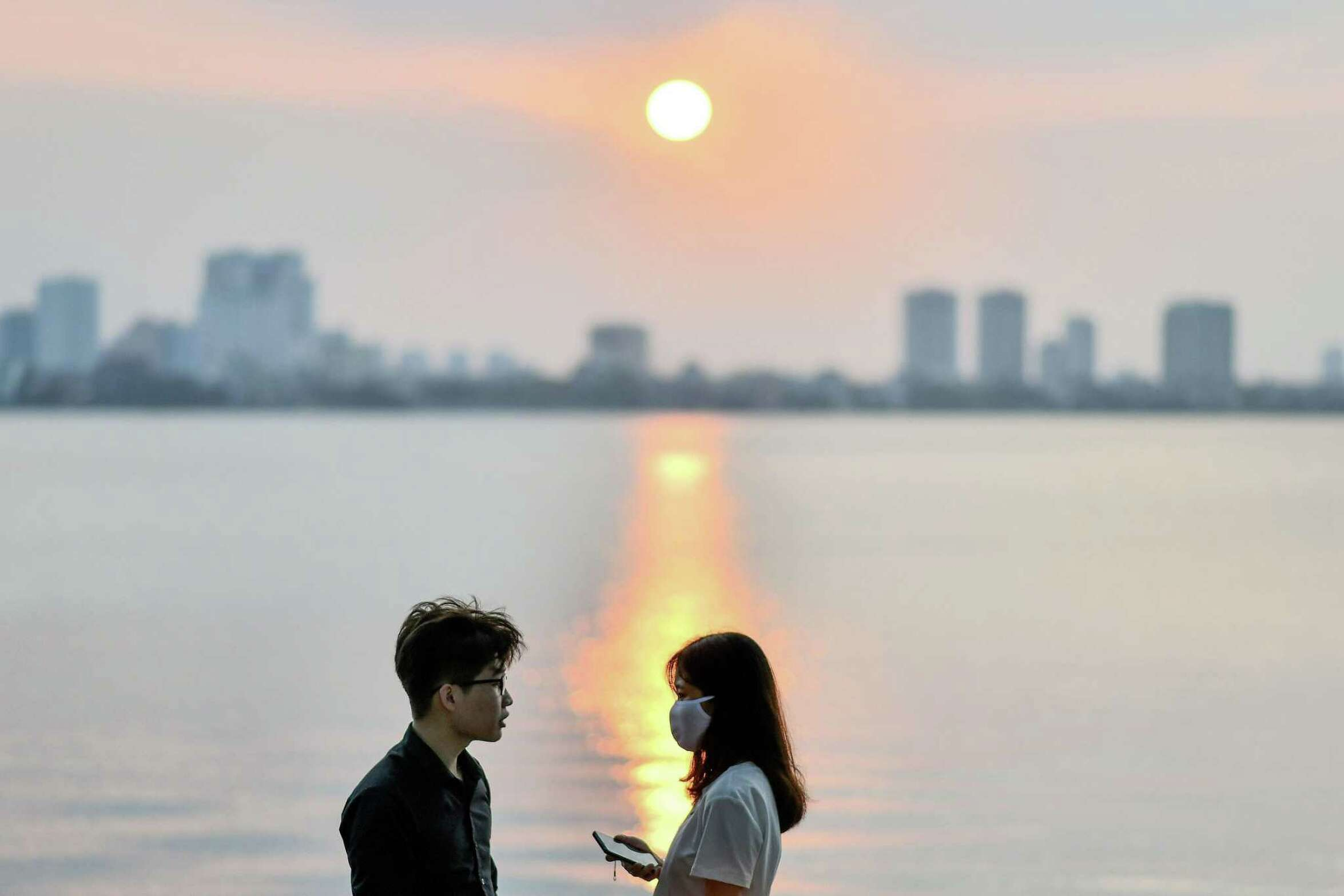 A girl (R), wearing a face mask as a preventive measure against the spread of the COVID-19 novel coronavirus, stands by the lakeside at sunset in Hanoi on May 2, 2020. (Photo by Manan VATSYAYANA / AFP) (Photo by MANAN VATSYAYANA/AFP via Getty Images)