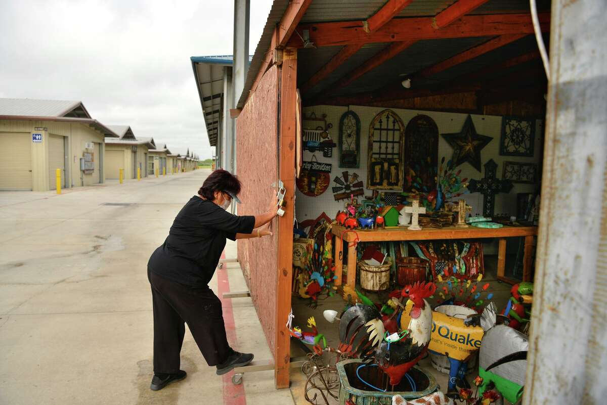 Maria Yupanqui locks up her Rustics At Maria's stall at Traders Village Saturday as it was closed after originally being scheduled to open. City officials told Village management would not be permitted to open.