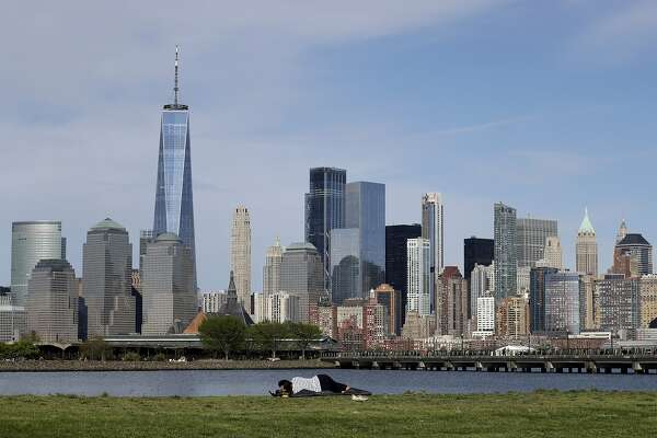 """A woman looks at the Manhattan skyline from Liberty State Park in Jersey City, N.J., Saturday, May 2, 2020. Gov. Phil Murphy said early reports of behavior at New Jersey's just-reopened parks and golf courses were """"so far so good"""" as far as people adhering to social distancing. Murphy earlier said state troopers and park police would closely watch parks and golf courses as they reopened during especially fine weather over the weekend. (AP Photo/Seth Wenig)"""