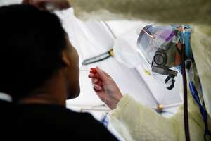 FILE - In this April 20, 2020, photo, a test is performed on a patient in a COVID-19 triage tent at St. Joseph's Hospital in Yonkers, N.Y.. (AP Photo/John Minchillo)