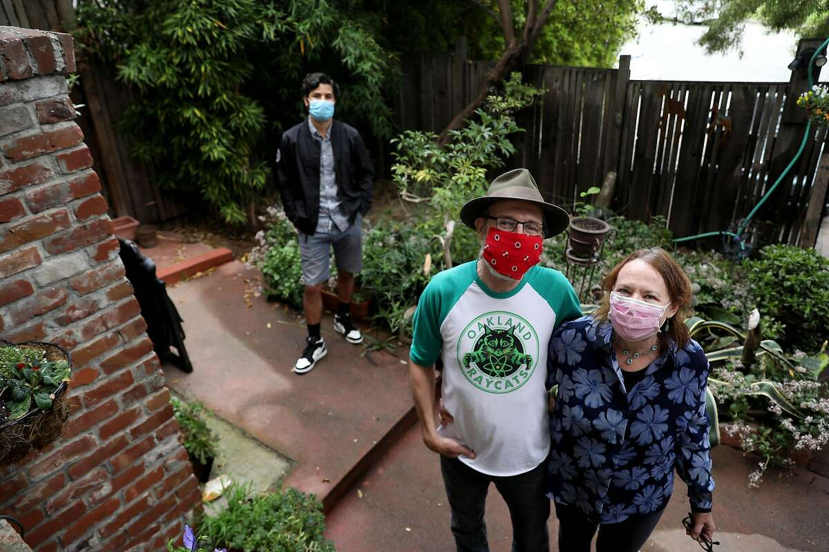 David Quintanilla, left, Oliver Kay and his wife Christina Sunley pose for a portrait at their home on Saturday, May 2, 2020, in Oakland, Calif. Kay and Sunley haven't set foot inside a store of any kind in five weeks. The couple registered online at Oaklandatrisk.com, a website that matches high-risk folks with low-risk folks who want to help. Quintanilla has been running errands for the couple.