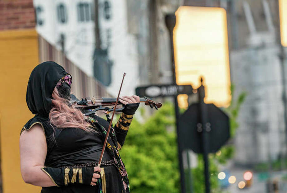 "ALTON — A mysterious, masked minstrel has been seen by many recently, shredding on a fiddle in downtown Alton in the areas of East Broadway, Third Street and Lincoln Douglas Square. When approached, she's asked not to be identified, only providing the moniker of ""Fiddle Assassin."" However, she's made it clear that her only enemy is the coronavirus. ""I'm out here to slay the virus,"" she told a Telegraph reporter. ""Really, I'm just out here to have some fun. We all need to wear masks when out [in public], so it's good to be able to have some fun with that."" She added that she really enjoys waves and honking horns from passing motorists, and attempts to break into Charlie Daniels' ""The Devil Went Down to Georgia"" whenever a swarm of motorcyclists approach. The ""Fiddle Assassin"" says she plans to be out playing the streets of Alton a couple times per week as the COVID-19 crisis persists. Photo: Nathan Woodside 