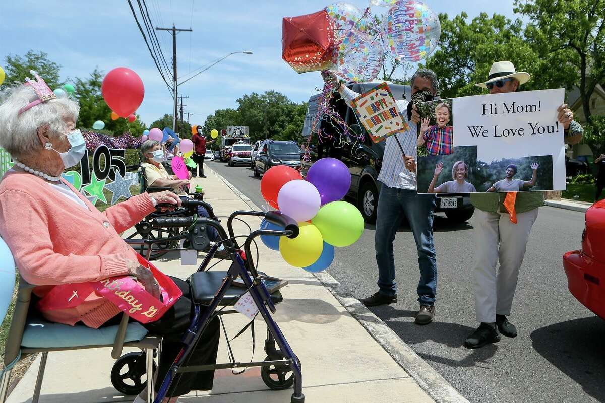 Irene Wilson, seated left, receives birthday wishes from her son-in-law Laurence Kurth, right, and Charlie Garza during a surprise parade celebrating her105th birthday, organized by the staff at Franklin Park Alamo Heights, the complex where she lives, on Wednesday, April 29, 2020.