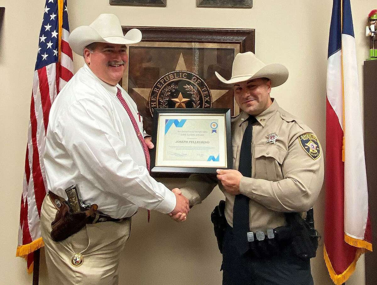 San Jacinto County Sheriff Greg Capers awards the Life-Saving Award to Deputy Sheriff Joseph Pellegrino after the deputy saved the life of the driver he had pulled over last Oct. 25.