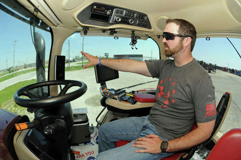 "Sievers Equipment sales representative Alex Veatch demonstrates the AFS Connect technology in the cab of a new Case-IH tractor. ""The technology exists for as much as you can tolerate,"" Veatch said."
