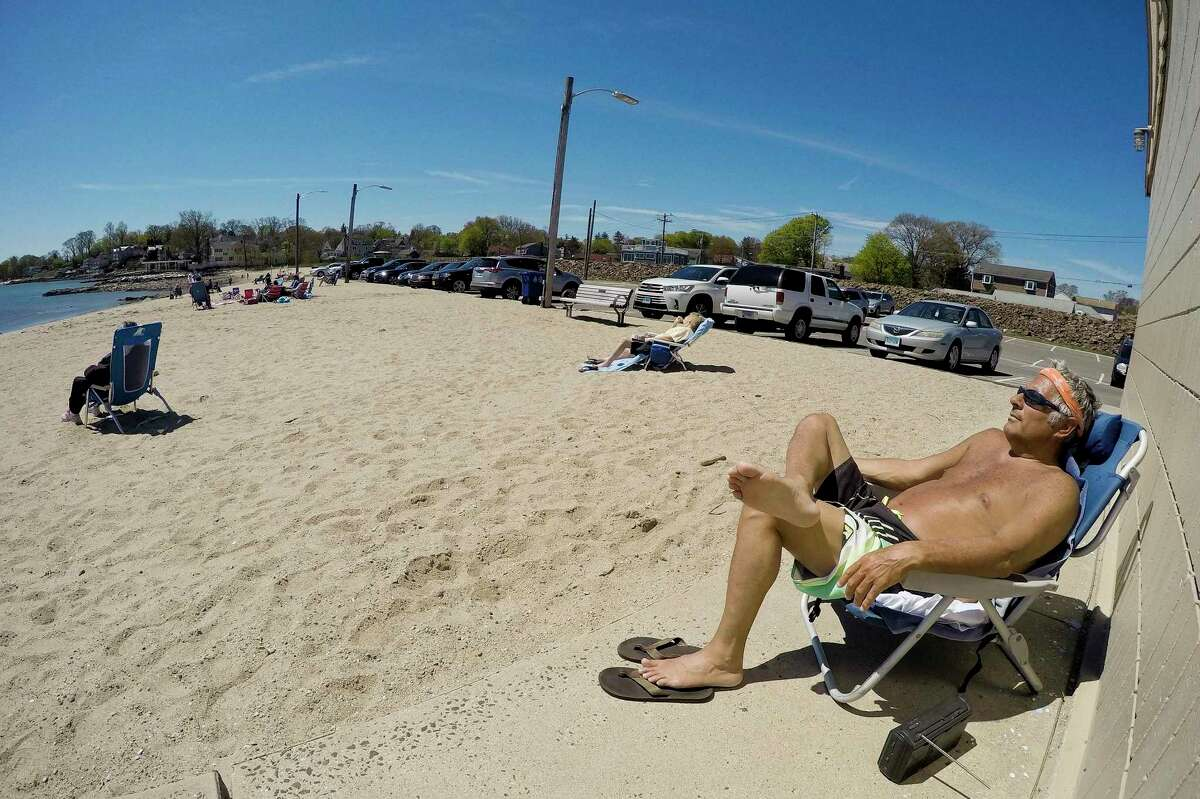 At right, Michael Lombardo of Stamford, listens to his radio while soaking up the sunshine and maintaining proper social distancing between fellow beach goers at West Beach in Stamford, Connecticut on May 2, 2020.