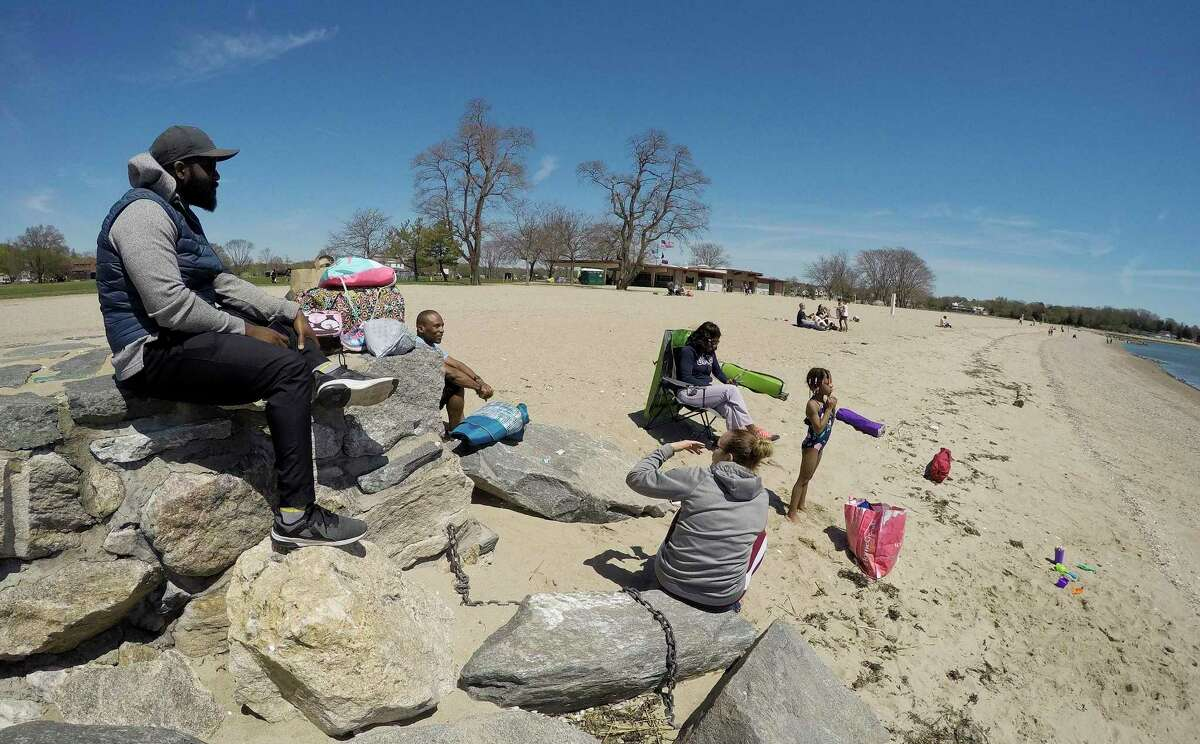 A family enjoys the sunshine while maintaining proper social distancing between fellow beach goers at Cove Island Beach in Stamford, Connecticut on May 2, 2020.
