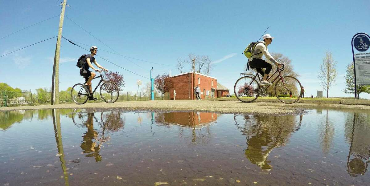 A pair of bicyclist are reflected in a puddle of water as they bike at Cove Island Park in Stamford, Connecticut on May 2, 2020.