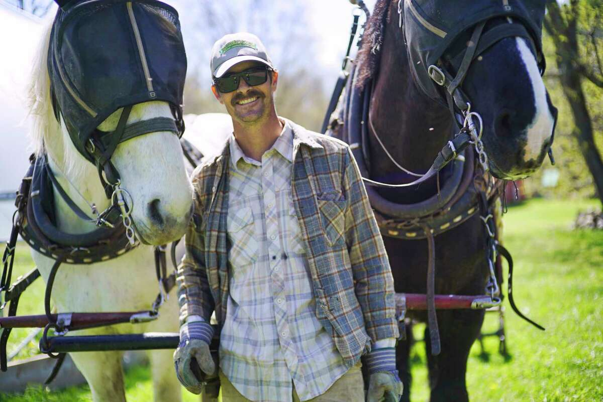 Tim Biello poses for a photo with his two Percheron draft horses, Bear and Duke, at Featherbed Lane Farm on Sunday, May 3, 2020, in Ballston Spa, N.Y. (Paul Buckowski/Times Union)