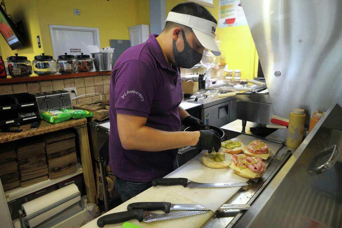 Chris Jarrin prepares lunch orders at Fruta Juice, in Bridgeport on Wednesday. The downtown deli remains open for online and takeout orders during the pandemic.