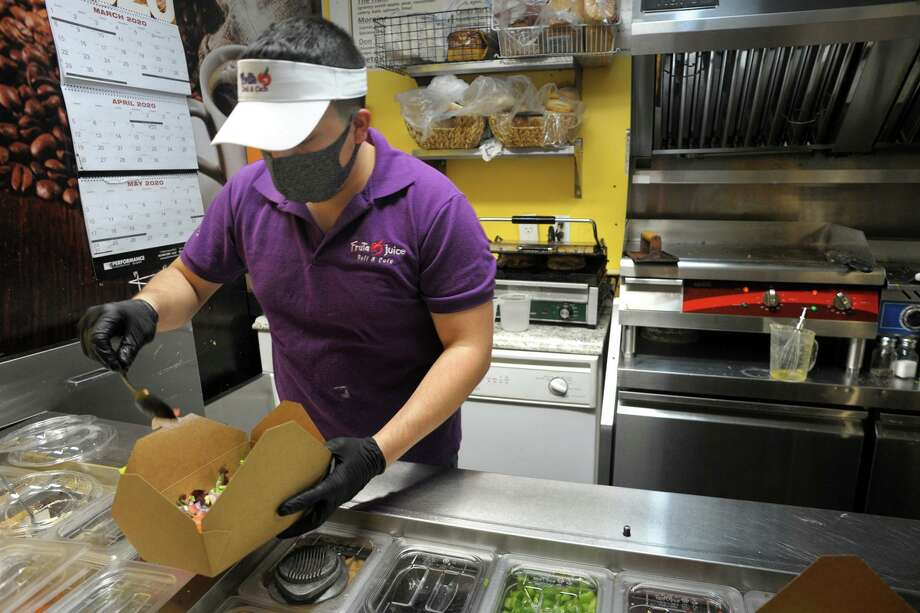 "Chris Jarrin prepares a takeout order in late April 2020 at Fruta Juice in Bridgeport, Conn. On May 20, Connecticut will begin reopening sectors of its economy in stages, with businesses required to certify safety measures they have taken and post a ""badge"" notifying visitors they have done so. Photo: Ned Gerard / Hearst Connecticut Media / Connecticut Post"