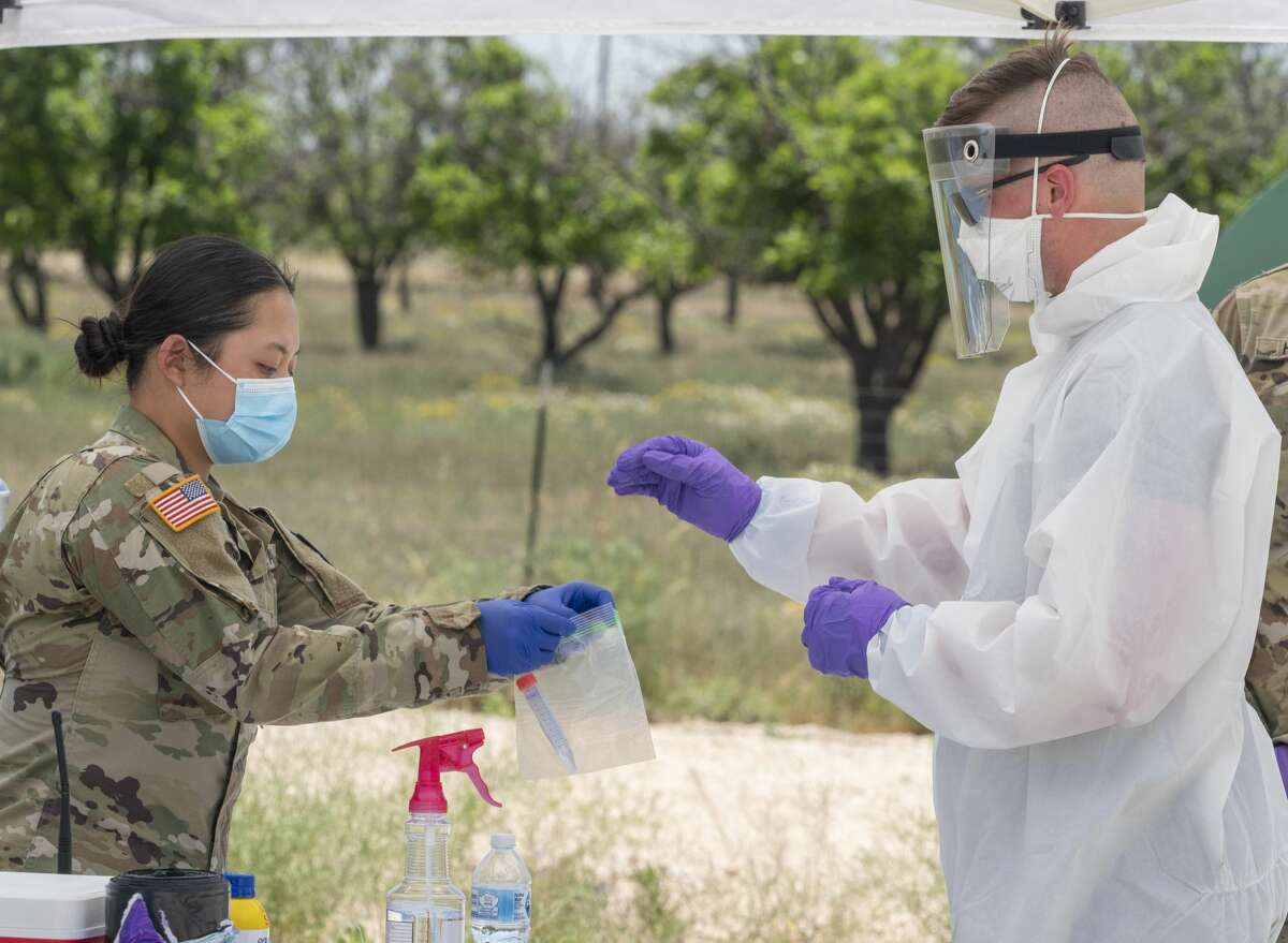 Sgt. Jon Murphy, medic with the 2nd 142nd INF out of Lubbock, TX, hands the nasal swab to Pvt. First Class Kelly Nguyen as they and other members of the Texas Military Forces, including the Texas Army National Guard, Texas Air National Guard, and Texas State Guard, conduct coronavirus testing 05/03/2020 at the Greenwood Volunteer Fire Department. The testing is free and open to anyone, but appointments had to be made in advance. Tim Fischer/Reporter-Telegram
