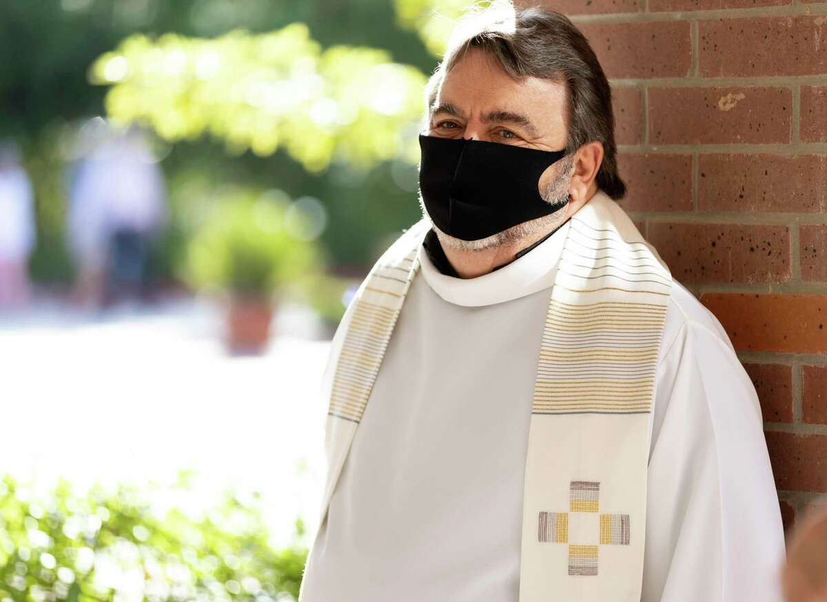 Reverend Thomas Rafferty pastor of Saint Anthony of Padua in The Woodlands greets parishioners as they wait in line to enter the church, Sunday, May 3, 2020. Gov. Greg Abbott's recent executive order allows churches to resume services following state guidelines.