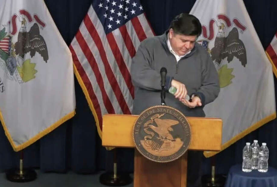 Gov. J.B. Pritzker applies hand sanitizer before beginning his daily news conference Sunday in Chicago. Pritzker on Sunday announced 2,994 new confirmed cases of COVID-19 in Illinois the past 24 hours, and 63 additional deaths. Photo: Blueroomstream.com