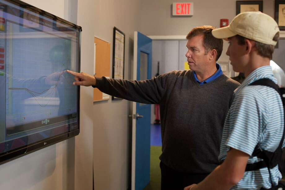 Roger Knck, left, helps out a junior golfer at the Golf Performance Center in Ridgefield. Photo: Contributed Photo / 2012