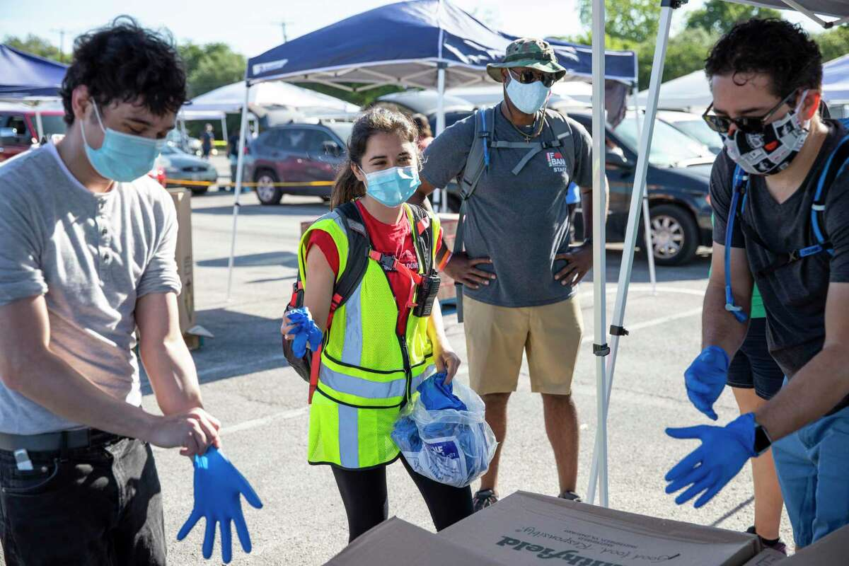 Brittany Jones, second left, passes out latex gloves to volunteers during a food distribution by the San Antonio Food Bank at the Alamodome in San Antonio, Texas, U.S, on Friday, May 1, 2020. Jones, a San Antonio native who graduated from Texas A&M at College Station, joined AmeriCorps to work with the San Antonio Food Bank where she has been organizing and distributing food to those in need during the coronavirus global pandemic.