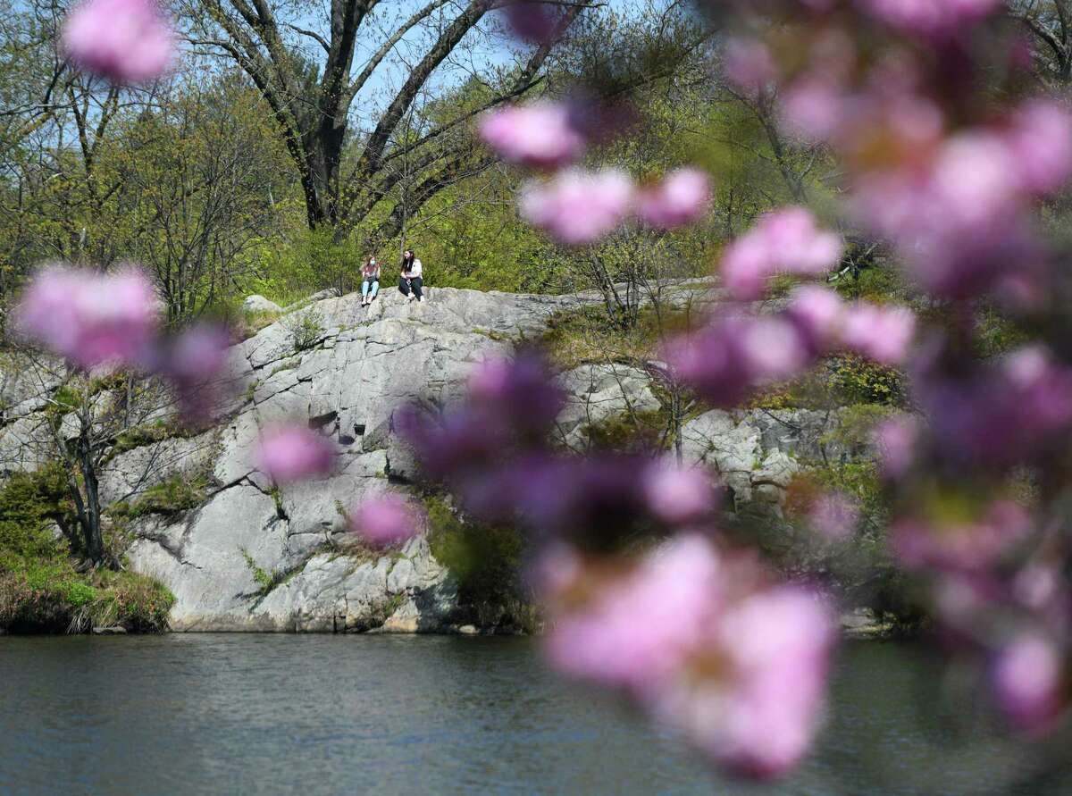Two people sit on a rock overlooking the water at Bruce Park on a sunny day in Greenwich, Conn. Sunday, May 3, 2020. With a high temperature in the upper-70s, the town saw lots of exhausted quarantiners active on the streets and in the parks.