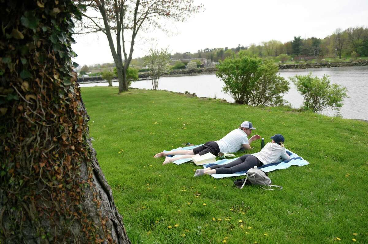 Greenwich residents Roman and Nicole Josiger catch some sun at Roger Sherman Baldwin Park on a sunny day in Greenwich, Conn. Sunday, May 3, 2020. With a high temperature in the upper-70s, the town saw lots of exhausted quarantiners active on the streets and in the parks.