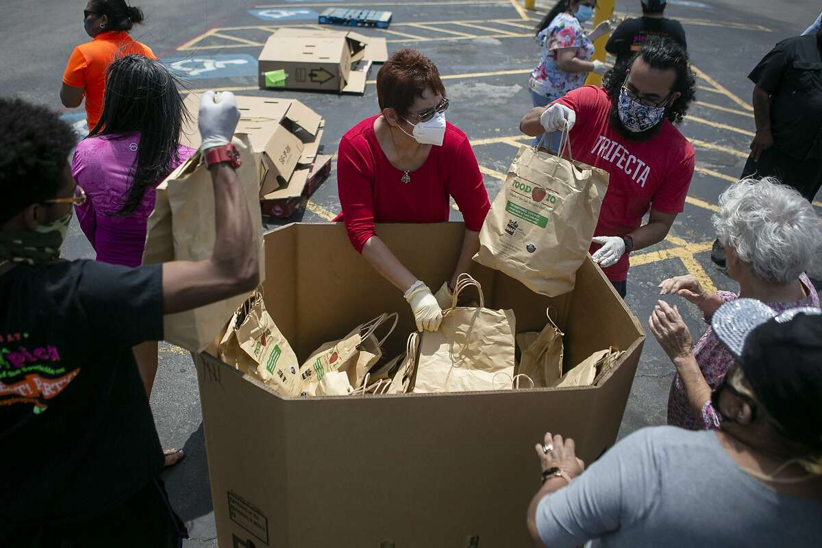 Volunteers place undistributed bags of food into a container during the Lots of Love and the San Antonio Food Bank distribution held at PicaPica Plaza in San Antonio, Texas on April 29, 2020. Pica Pica Plaza Ownership Group and Flip?•z Entertainment says it has raised more than $450,000 for the San Antonio Food Bank through its Lots of Love Initiative developed by Al Honigblum, managing partner of PicaPica Plaza Ownership Group.
