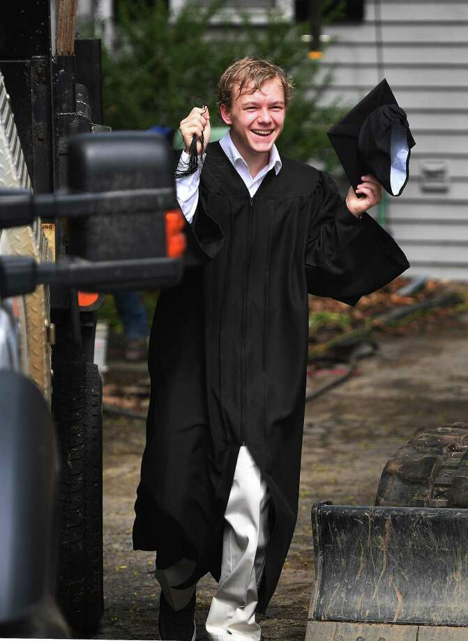 P-Tech program graduate Landon Heatley greets program staffers as he comes out to take cap and gown photos outside his home in Norwalk, Conn. on Sunday, May 3, 2020. Staffers in a car caravan visited each of the program graduates for photos on Sunday. Photo: Brian A. Pounds / Hearst Connecticut Media / Connecticut Post