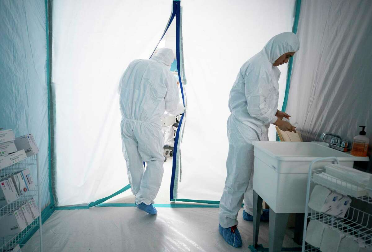 Physicians enter the double isolation wing at United Memorial Medical Center, where COVID-19 patients needing intensive care are being treated. Photographed Tuesday, April 28, 2020, in Houston.