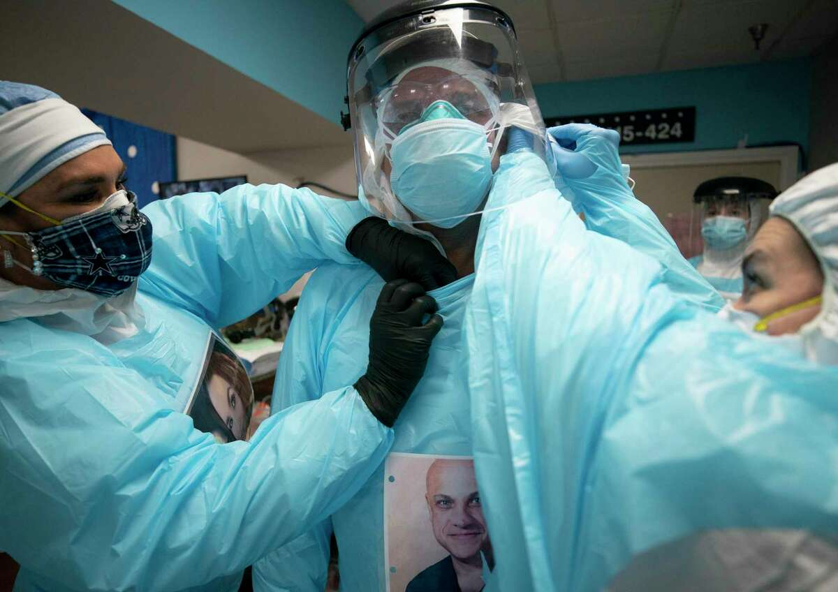 Nurses help Dr. Joseph Varon, center, get into the PPE required to enter the COVID-19 intensive care unit at UMMC on Tuesday, April 28, 2020, in Houston.