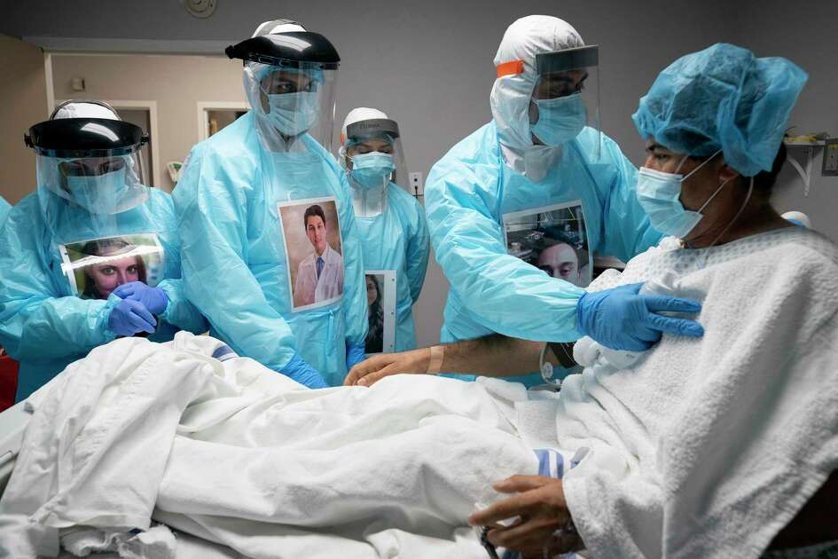Juan Carlos Peña, 43, is checked on by physicians and nurses before administering an ultrasound on his lungs at UMMC's COVID-19 intensive care unit Tuesday, April 28, 2020, in Houston. Peña decided to go to the hospital after spending a week with a fever, body ache, and nonstop coughing.