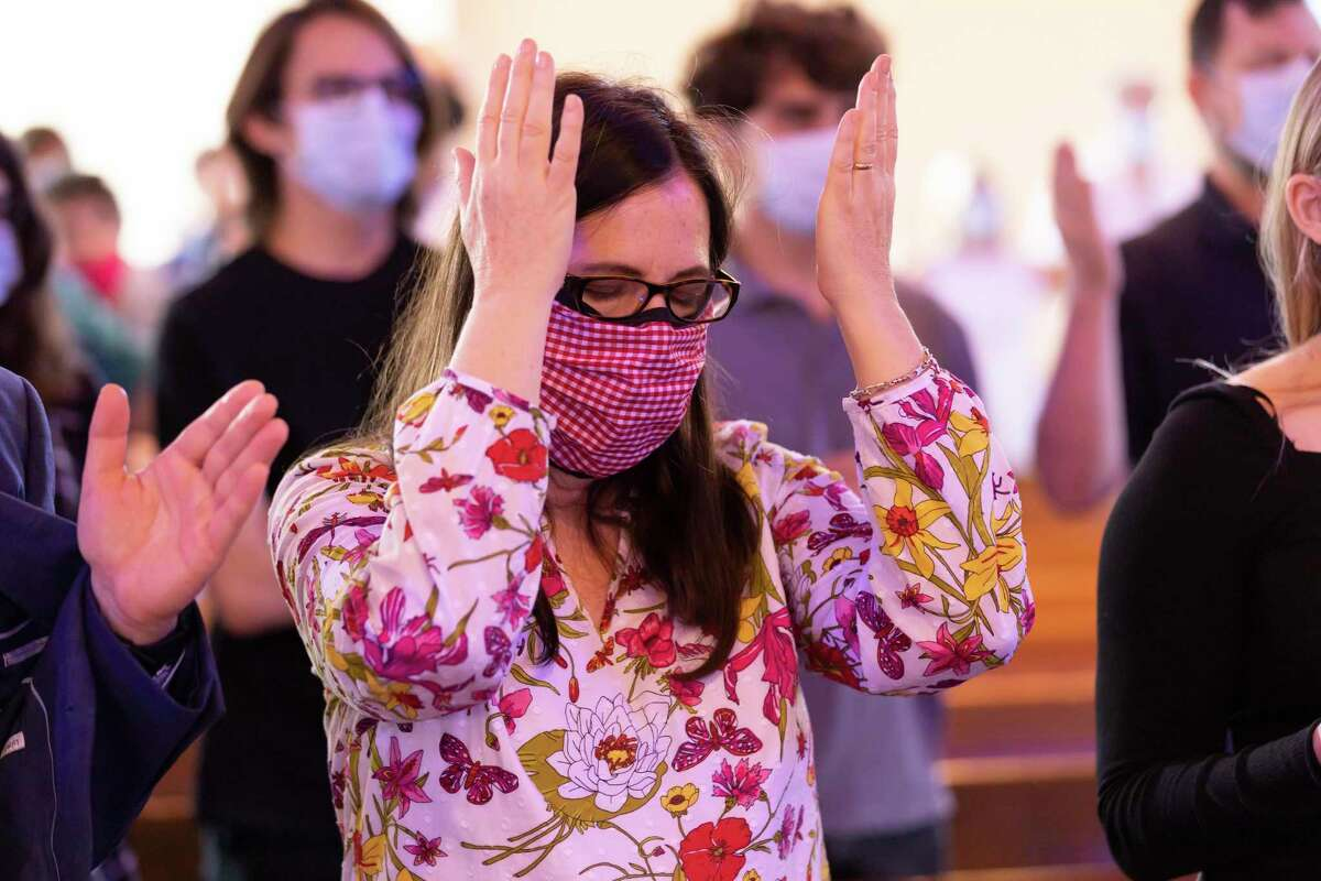 A parishioner prays after accepting the sacrament at Saint Anthony of Padua in The Woodlands, Sunday, May 3, 2020. Gov. Greg Abbott's recent executive order allows churches to resume services following state guidelines.