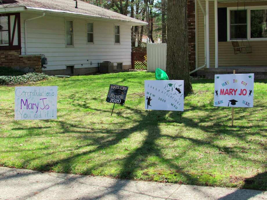 Signs decorate Mary Jo LaRue's yardon Friday, May 1. LaRue graduated with a Master of Social Work from Michigan State University. (Victoria Ritter/vritter@mdn.net)