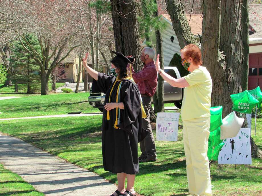 Mary Jo LaRue waves at passing cars with neighbors Mike and Carol Buller on Friday, May 1. In addition to the PEO Chapter CE drive-by, neighbors arranged a second surprise celebration to honor LaRue's graduation from Michigan State University. (Victoria Ritter/vritter@mdn.net)